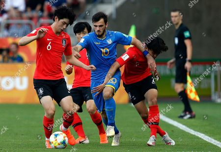 Ukraine's Serhii Buletsa, center, duels for the ball with South Korea's Kim Jung-min, left, and South Korea's Hwang Tae-hyeon during the final match between Ukraine and South Korea at the U20 soccer World Cup in Lodz, Poland