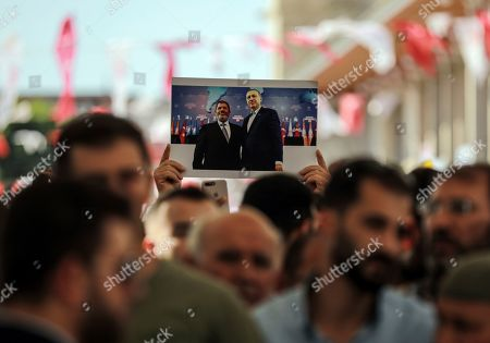 Supporters join Turkish President Recep Tayyip Erdogan, who attends funeral prayers in absentia for ousted former Egyptian President Mohammed Morsi, as an image of Erdogan with Morsi is held at Fatih Mosque in Istanbul, . Funeral prayers were held in mosques across Turkey for Morsi, who had close ties to Erdogan. The former president, who was ousted by current President Abdel-Fattah el-Sissi in a military coup in 2013, collapsed in a courtroom in Egypt during trial on Monday and died