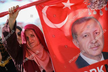 Supporters join Turkish President Recep Tayyip Erdogan, image seen on flag, who attends funeral prayers in absentia for ousted former Egyptian President Mohammed Morsi, at Fatih Mosque in Istanbul, . Funeral prayers were held in mosques across Turkey for Morsi, who had close ties to Erdogan. The former president, who was ousted by current President Abdel-Fattah el-Sissi in a military coup in 2013, collapsed in a courtroom in Egypt during trial on Monday and died