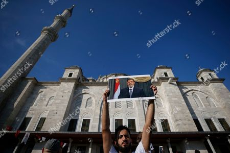 Supporters join Turkish President Recep Tayyip Erdogan, who attends funeral prayers in absentia for ousted former Egyptian President Mohammed Morsi, seen in poster, at Fatih Mosque in Istanbul, . Funeral prayers were held in mosques across Turkey for Morsi, who had close ties to Erdogan. The former president, who was ousted by current President Abdel-Fattah el-Sissi in a military coup in 2013, collapsed in a courtroom in Egypt during trial on Monday and died