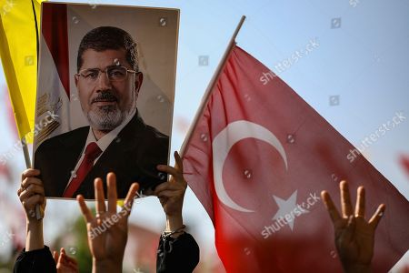 Supporters join Turkish President Recep Tayyip Erdogan, who attends funeral prayers in absentia for ousted former Egyptian President Mohammed Morsi, in poster, at Fatih Mosque in Istanbul, . Funeral prayers were held in mosques across Turkey for Morsi, who had close ties to Erdogan. The former president, who was ousted by current President Abdel-Fattah el-Sissi in a military coup in 2013, collapsed in a courtroom in Egypt during trial on Monday and died