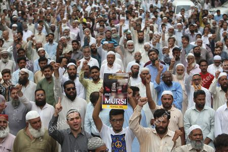 Supporters of the Pakistani religious party Jamaat-i-Islami, gather to offer a funeral prayer in absentia for ousted former Egyptian President Mohammed Morsi, in Karachi, Pakistan. . Morsi, Egypt's first democratically elected president ousted by the military in 2013, collapsed during a trial session in Cairo on Monday and died