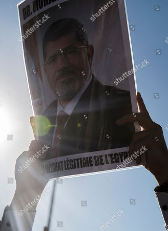 A man holds a picture of ousted former Egyptian President Mohammed Morsi in Tunis, Tunisia. . The former president, who was ousted by current President Abdel-Fattah el-Sissi in a military coup in 2013, collapsed in a courtroom in Egypt during trial on Monday and died