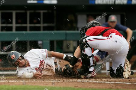 Will Holland, Henry Davis. Auburn's Will Holland (17) is tagged out at home plate by Louisville catcher Henry Davis in the third inning of an NCAA College World Series baseball game in Omaha, Neb