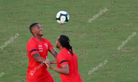 Ecuador's Antonio Valencia, left, and Arturo Mina view the ball during a training session for the Copa America in Salvador, Brazil