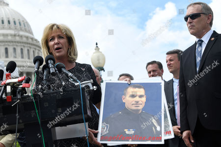 Stock Image of Andy Biggs, Mary Ann Mendoza. Rep. Andy Biggs, R-Ariz., right, listens as Angel Families Founder Mary Ann Mendoza, left, speaks as she holds a photo of her son, Police Officer Brandon Mendoza, who was was killed by an person who had entered the country illegally, during a news conference on Capitol Hill in Washington