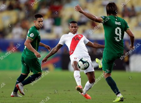Peru's Andy Polo, center, fights for the ball with Bolivia's Marcelo Martins Moreno, right, during a Copa America Group B soccer match at Maracana stadium in Rio de Janeiro, Brazil