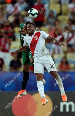 Bolivia's Adrian Jusino, left, and Peru's Jefferson Farfan go for a header during a Copa America Group B soccer match at Maracana stadium in Rio de Janeiro, Brazil