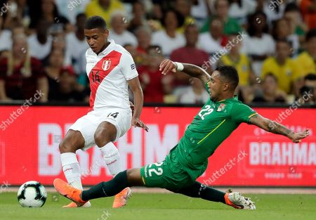Peru's Andy Polo fights for the ball with Bolivia's Adrian Jusino during a Copa America Group B soccer match at Maracana stadium in Rio de Janeiro, Brazil