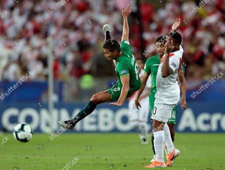 Bolivia's Diego Bejarano, left, fights for the ball with Peru's Jefferson Farfan during a Copa America Group B soccer match at Maracana stadium in Rio de Janeiro, Brazil