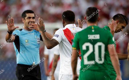 Referee Roddy Zambrano issues a verbal warning to Peru's Jefferson Farfan, center, during a Copa America Group B soccer match at Maracana stadium in Rio de Janeiro, Brazil