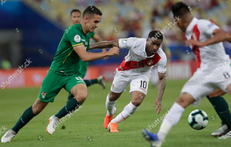 Peru's Jefferson Farfan, center, fights for the ball with Bolivia's Luis Haquin, left, during a Copa America Group B soccer match at Maracana stadium in Rio de Janeiro, Brazil