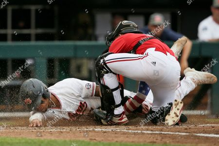 Stock Image of Auburn's Will Holland (17) is tagged out at home plate by Louisville catcher Henry Davis in the third inning of an NCAA College World Series baseball game in Omaha, Neb