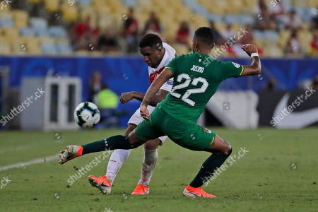 Bolivia's Adrian Jusino, 22, blocks a strike by Peru's Jefferson Farfan during a Copa America Group A soccer match at the Maracana stadium in Rio de Janeiro, Brazil