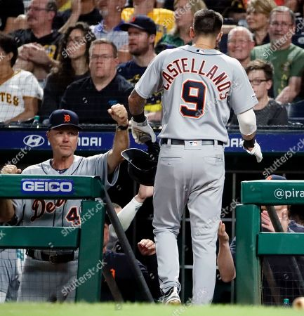 Detroit Tigers' Nicholas Castellanos (9) is greeted by bench coach Steve Liddle, left, after scoring on a ground out by Brandon Dixon off Pittsburgh Pirates relief pitcher Kyle Crick during the eighth inning of the team's baseball game in Pittsburgh, . The Tigers won 5-4