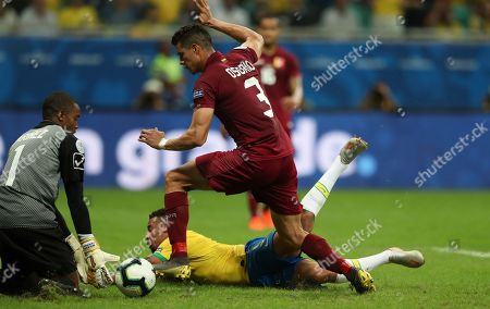 Brazil's Gabriel Jesus, on the ground, fights for the ball with Venezuela's Yordan Osorio, right, and Venezuela's goalkeeper Wuilker Farinez during a Copa America Group A soccer match at the Arena Fonte Nova in Salvador, Brazil