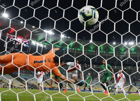 Jefferson Farfan of Peru scores his side's second goal despite the efforts of the Bolivian goalkeeper Carlos Lampe