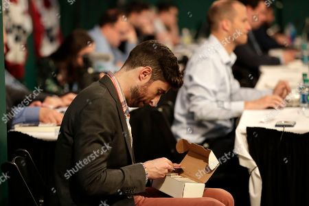 Stock Picture of Host Scott Rogowsky looks at a box of trading cards during the first round of the Major League Baseball draft, in Secaucus, N.J