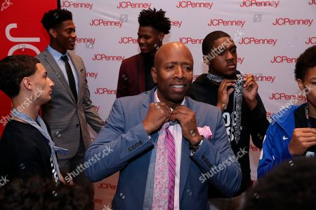 NBA legend Kenny Smith teaches young men from the Boys & Girls Club how to tie a tie during a styling session provided by JCPenney at the Moxy NYC Downtown, in New York