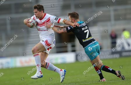 Louie McCarthy-Scarsbrook of St Helens tries to outrun Richie Myler of Leeds Rhinos