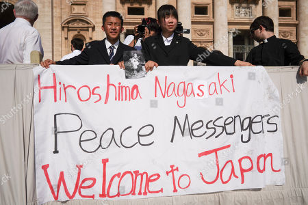 Uchiyama Koshiro, from Nagasaki, center left, and Matsuda Koharu, from Hiroshima, center right, both 16, hold a photo by U.S. photographer Joseph Roger O'Donnell of child victims of the Nagasaki atomic bombing, as they attend Pope Francis' weekly general audience in St. Peter's Square, at the Vatican