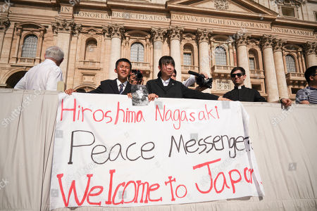 Uchiyama Koshiro, from Nagasaki, Japan, center left, and Matsuda Koharu, from Hiroshima, center right, both 16, hold a photo by U.S. photographer Joseph Roger O'Donnell of child victims of the Nagasaki atomic bombing, as they attend Pope Francis' weekly general audience in St. Peter's Square, at the Vatican