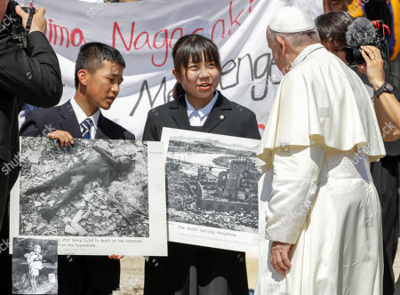 Japanese teenagers Uchiyama Koshiro, from Nagasaki, left, and Matsuda Koharu, from Hiroshima, both 16, hold historical photos, including a photo by U.S. photographer Joseph Roger O'Donnell of child victims, bottom left, of the atomic bombings in Nagasaki and Hiroshima, as they attend Pope Francis' weekly general audience in St. Peter's Square, at the Vatican