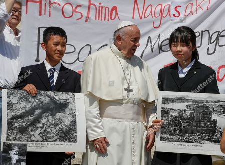 Japanese teenagers Uchiyama Koshiro, from Nagasaki, left, and Matsuda Koharu, from Hiroshima, both 16, hold historical photos, including a photo by U.S. photographer Joseph Roger O'Donnell of child victims, bottom left, of the atomic bombings in Nagasaki and Hiroshima, as they pose with Pope Francis at his weekly general audience in St. Peter's Square, at the Vatican
