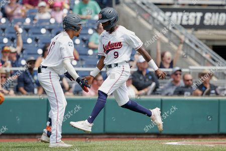 Ryan Bliss, Will Holland. Auburn's Ryan Bliss (9) is greeted by Auburn's Will Holland, left, after he scored a run against Louisville on a double by Conor Davis in the seventh inning of an NCAA College World Series baseball game in Omaha, Neb