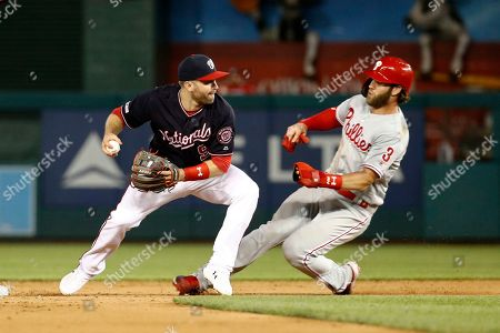 Stock Picture of Brian Dozier, Bryce Harper. Washington Nationals second baseman Brian Dozier, left, throws to first base after forcing out Philadelphia Phillies' Bryce Harper at second on Rhys Hoskins' fielder's choice ground ball in the sixth inning of the second baseball game of a doubleheader, in Washington. Hoskins was safe at first