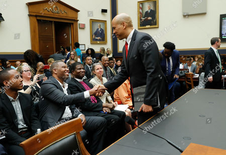 Democratic Presidential candidate Sen. Cory Booker, D-N.J., right, stops to shakes hands with with author Ta-Nehisi Coates, second from the left, as he waits to testify about reparation for the descendants of slaves during a hearing before the House Judiciary Subcommittee on the Constitution, Civil Rights and Civil Liberties, at the Capitol in Washington