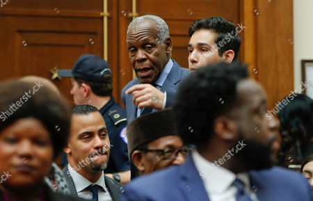 Actor Danny Glover, center, is directed to his seat before his scheduled testimony about reparation for the descendants of slaves during a hearing before the House Judiciary Subcommittee on the Constitution, Civil Rights and Civil Liberties, at the Capitol in Washington