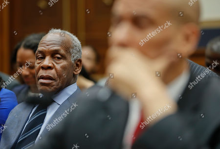 Actor Danny Glover, left, looks over at Democratic Presidential candidate Sen. Cory Booker, D-N.J., right, as Booker waits to testify about reparation for the descendants of slaves during a hearing before the House Judiciary Subcommittee on the Constitution, Civil Rights and Civil Liberties, at the Capitol in Washington