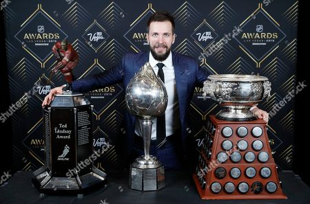 Tampa Bay Lightning's Nikita Kucherov poses with, from left, the Ted Lindsay Award, Hart Memorial Trophy and the Art Ross Trophy after winning the honors at the NHL Awards, in Las Vegas