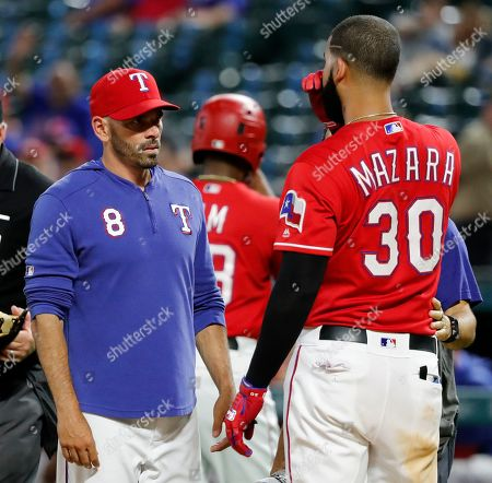 Chris Woodward, Nomar Mazara. Texas Rangers manager Chris Woodward (8) checks on Nomar Mazara (30), who was hit by a pitch thrown by Cleveland Indians' Adam Cimber in the ninth inning of a baseball game in Arlington, Texas, . The ball initially hit Mazara on the hip, then ricocheted and also hit him on the face. Mazara remained in the game
