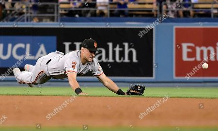 San Francisco Giants second baseman Joe Panik can't reach a ball hit for a single by Los Angeles Dodgers' David Freese during the seventh inning of a baseball game, in Los Angeles