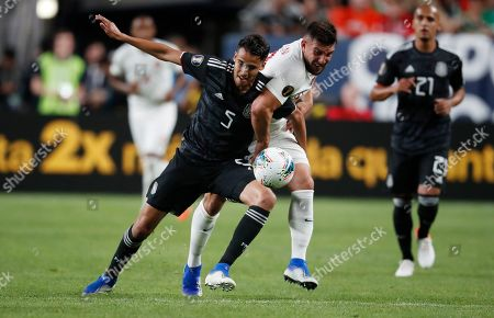 Mexico defender Diego Reyes, left, fights for control of the ball with Canada forward Lucas Cavallini during the first half of a CONCACAF Gold Cup soccer match, it Mile High Stadium in Denver