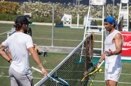 Spanish tennis player Rafa Nadal (R) chats with his coach, Carlos Moya (L), as he attends a training session at Country Club in Santa Ponsa, Majorca, Spain, 20 June 2019. Nadal prepares for the upcoming Wimbledon Championships.