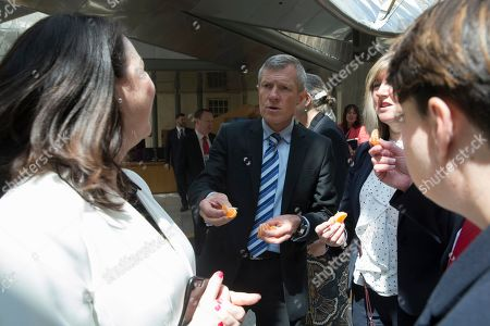 The Great Get Together (inspired by the murdered MP, Jo Cox) photocall at The Scottish Parliament - Willie Rennie, Leader of the Scottish Liberal Democrats, offers a piece of satsuma to Monica Lennon, sponsor of the event, while they wait for the photocall to begin