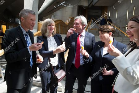 The Great Get Together (inspired by the murdered MP, Jo Cox) photocall at The Scottish Parliament - while waiting for the photocall to begin, a satsuma is shared by Willie Rennie, Leader of the Scottish Liberal Democrats, with Alison Johnstone, Co-Leader of the Scottish Greens in the Scottish Parliament, Richard Leonard, Leader of the Scottish Labour Party, Ruth Davidson, Leader of the Scottish Conservative and Unionist Party, and Monica Lennon, sponsor of the event.