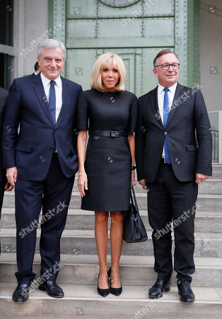 "Sidney Toledano, left, Brigitte Macron wife of French President Emmanuel Macron, center, and Bruno Pavlovsky president of Chanel arrive at the event named ""Karl for Ever"" at the Grand Palais in Paris, France, . The event pays tribute to late German fashion designer Karl Lagerfeld who died Feb. 19, 2019"