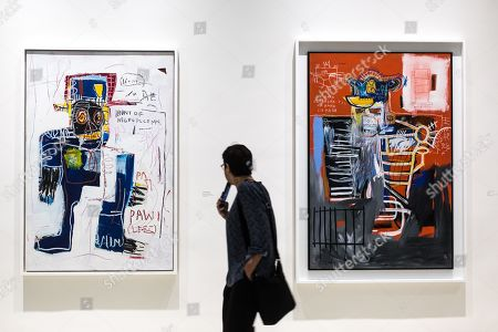 A visitor looks on artworks, including 'La Hara' (R) by American artist Jean-Michel Basquiat on display at the 'Basquiat's Defacement' Exhibition in the Solomon R. Guggenheim Museum in New York, New York, USA, 20 June 2019. The exhibition runs from 21 June to 06 November 2019.