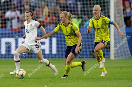 Stock Photo of United States' Rose Lavelle, left, takes the ball away from Sweden's Amanda Ilestedt and Caroline Seger, right, during the Women's World Cup Group F soccer match between Sweden and the United States at Stade Océane, in Le Havre, France