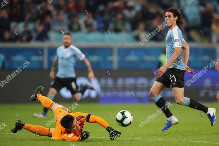 Japan's goalkeeper Eiji Kawashima, left, blocks a shoot by Uruguay's Edinson Cavani during a Copa America Group C soccer match at the Arena Gremio in Porto Alegre, Brazil