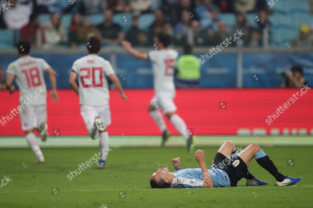 Uruguay's Diego Laxalt lying on the pitch as Japan players celebrate their side's first goal during a Copa America Group C soccer match at the Arena Gremio in Porto Alegre, Brazil