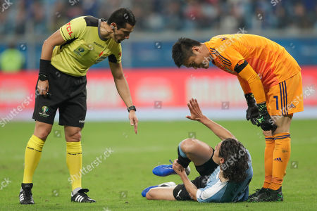 Referee Andres Rojas, left, talks to Uruguay's Edinson Cavani, center, as Japan's goalkeeper Eiji Kawashima, right, looks on during a Copa America Group C soccer match between Uruguay and Japan at the Arena Gremio in Porto Alegre, Brazil