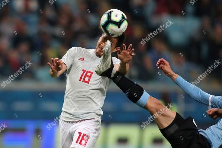 Japan's Shinji Okazaki, left, jumps for a header challenged by Uruguay's Rodrigo Bentancur during a Copa America Group C soccer match at the Arena Gremio in Porto Alegre, Brazil