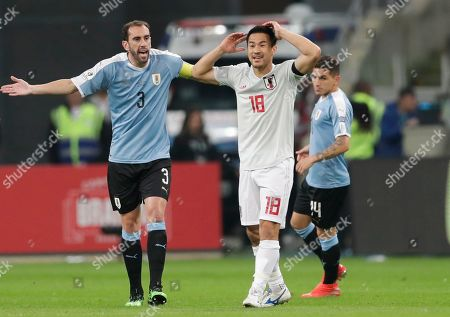 Japan's Shinji Okazaki, right, reacts next to Uruguay's Diego Godin during a Copa America Group C soccer at the Arena Gremio in Porto Alegre, Brazil