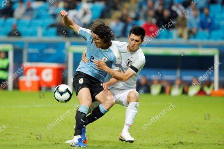 Edinson Cavani (L) of Uruguay in action against Naomichi Ueda (R) of Japan during the Copa America 2019 Group C soccer match between Uruguay and Japan, at Arena do Gremio Stadium in Porto Alegre, Brazil, 20 June 2019.
