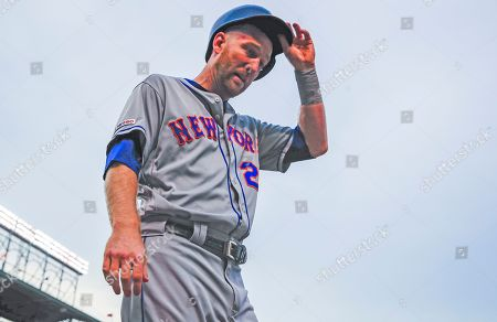 New York Mets third baseman Todd Frazier removes his batting helmet as he walks to the dugout after scoring on an RBI double play hit into by New York Mets center fielder Carlos Gomez in the second inning of the MLB baseball game between the New York Mets and the Chicago Cubs at Wrigley Field in Chicago, Illinois, USA, 20 June 2019.
